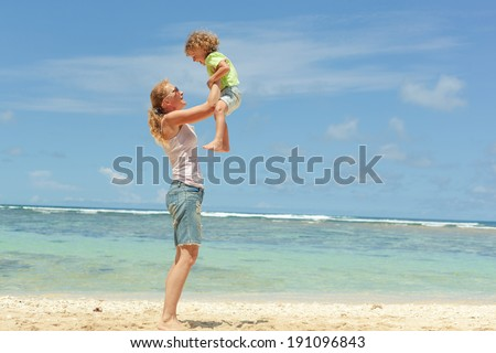 mother and  son playing on the beach in day time - stock photo