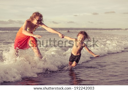 mother and  son playing on the beach in the day time - stock photo
