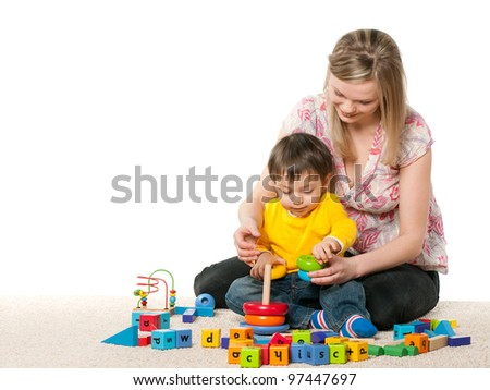 Mother and son playing on the carpet with toys; isolated on the white background - stock photo