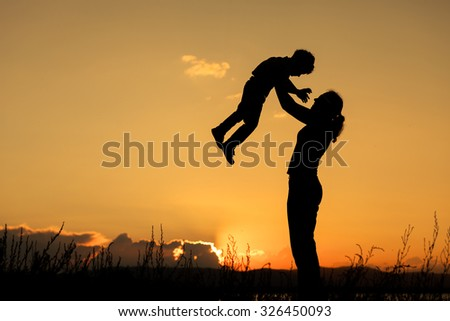 Mother and son playing on the coast of lake in the mountains of at the sunset time.  Concept of friendly family. - stock photo