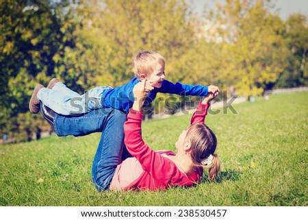 mother and son playing outdoors in autumn park - stock photo