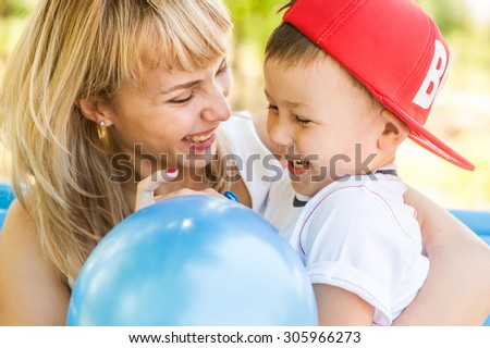 Mother and son playing together outdoors in park with soap bubbles - stock photo