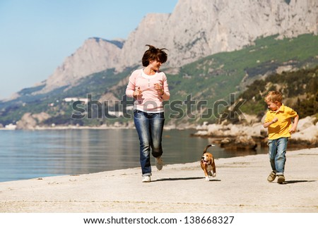 Mother and son playing with beagle puppy at the sea coast - stock photo