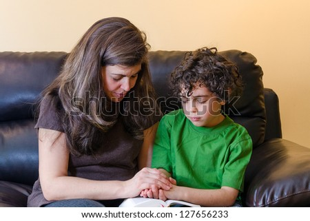 Mother and son praying  at home - stock photo
