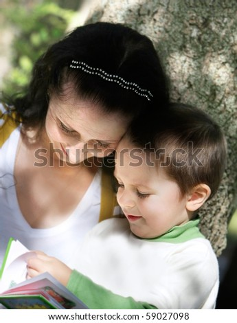 mother and son reading book outdoors - stock photo