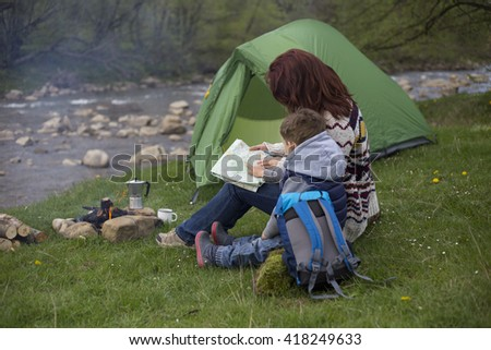 Mother and son sit near the fire and looking at the map. - stock photo