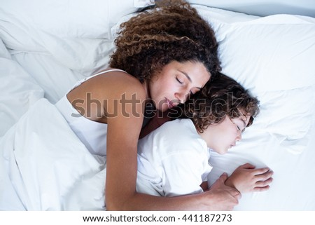 Mother and son sleeping together on bed - stock photo