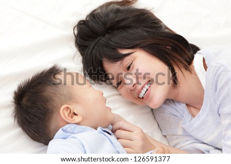 Mother and son smile and look each other and lying on white bed in the bedroom at home, asian family - stock photo