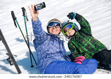 Mother and son take a selfie photo on ski resort - stock photo
