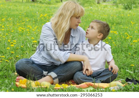 Mother and son talking among dandelion field - stock photo