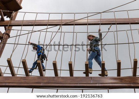 Mother and son together on an obstacle course - stock photo