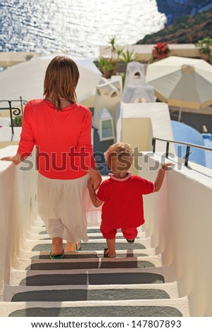 mother and son walking in Santorini, Greece - stock photo