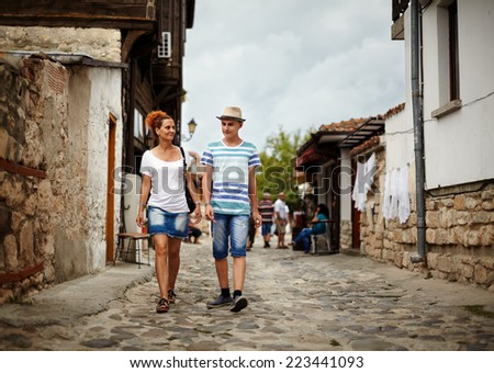 Mother and son walking on an alley in an ancient touristic town - stock photo