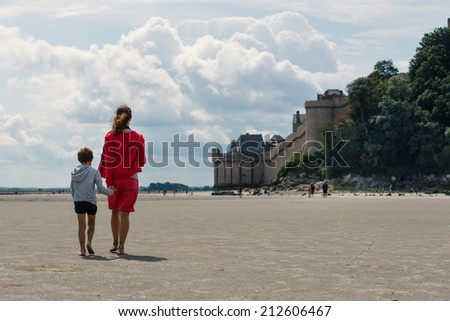 Mother and son walking on the beach in front of Mont Saint Michel ancient village. Normandy, France. - stock photo