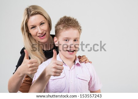 Mother and son with blond hair doing thumbs up in the studio - stock photo