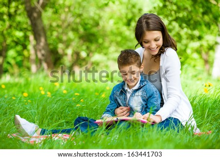 Mother and son with book sitting on green grass in park. Concept of happy family relations and carefree leisure time - stock photo