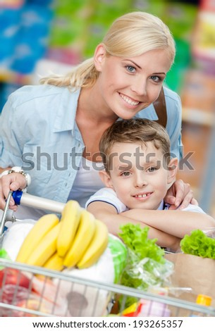 Mother and son with cart full of products in shop. Concept of healthy food and consumerism - stock photo