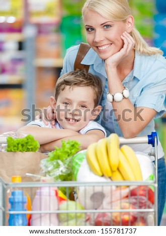 Mother and son with cart full of products in shopping mall. Concept of healthy food and consumerism - stock photo