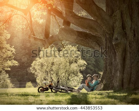 Mother and son with them bicycles in the park under sunlight. - stock photo