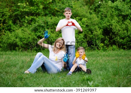 Mother and sons playing on the background of green trees. Mom and sons hands smeared with colored paint. - stock photo