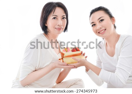 Mother and teenager daughter holding with cake - stock photo
