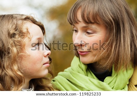 Mother and teenager daughter looking at each other while walking in an autumn park - stock photo