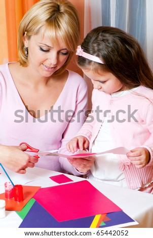 Mother and the daughter cut figures from a colour paper - stock photo