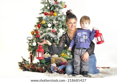 Mother and their small child sits near Christmas tree with red lamps - stock photo