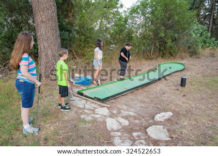 Mother and three children playing outdoor miniature golf in a Galilee forest in the north of Israel - stock photo