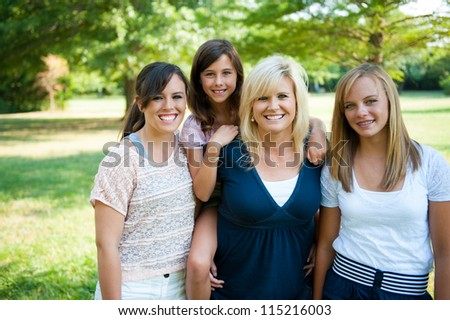 Mother and three daughters oustide smiling - stock photo