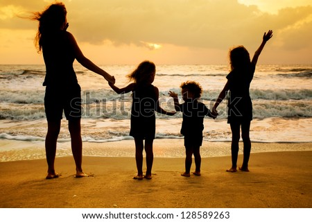 Mother and three kids silhouettes standing on beach at sunset - stock photo