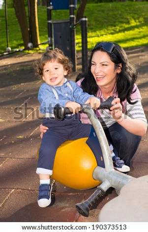 Mother and toddler son having fun in park  and boy sitting on seesaw - stock photo