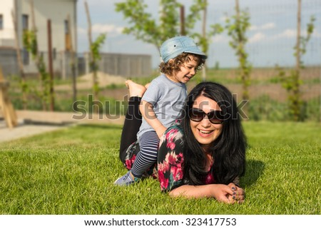 Mother and toddler son having fun outside at countryside - stock photo