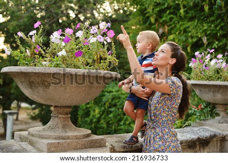 mother and toddler son near the flowers - stock photo
