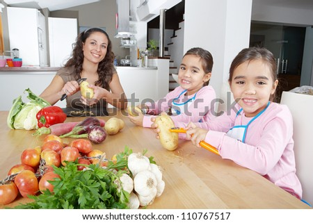 Mother and twin daughters learning to peel potatoes together in the kitchen, using a chopping board with fruit and vegetables. - stock photo