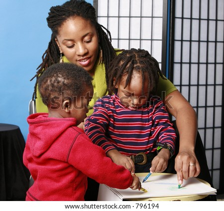 Mother and two boys drawing with crayons - stock photo