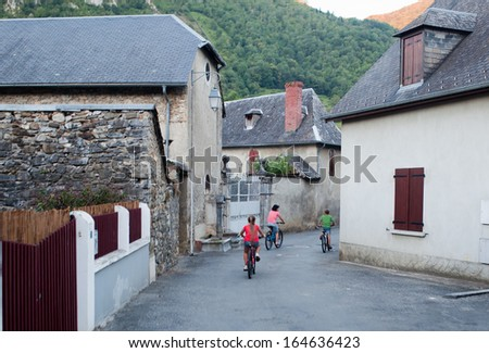 Mother and two children ride on cycles through a Beaudean village on a summer evening (France) - stock photo