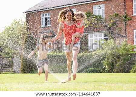 Mother And Two Children Running Through Garden Sprinkler - stock photo
