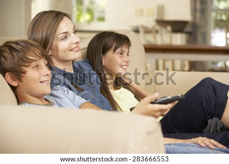 Mother And Two Children Sitting On Sofa At Home Watching TV Together - stock photo