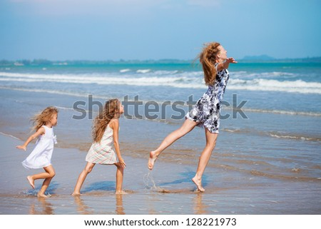 mother and two daughters jumping on the beach - stock photo