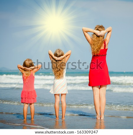 mother and two daughters standing on the beach - stock photo