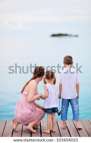 Mother and two kids at wooden dock enjoying ocean view - stock photo