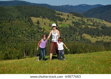 Mother and two kids having fun outdoors - stock photo