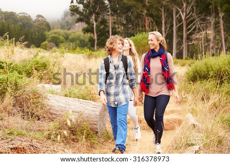 Mother and two kids walking on a forest trail - stock photo