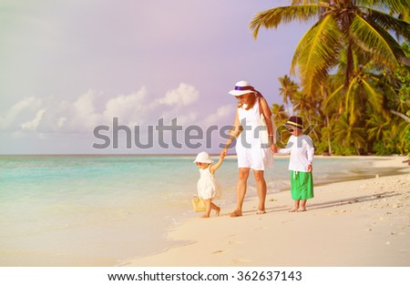 mother and two kids walking on tropical beach - stock photo