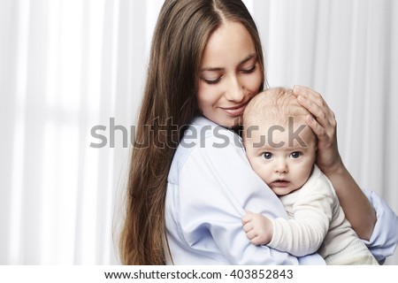Mother and young baby embracing - stock photo