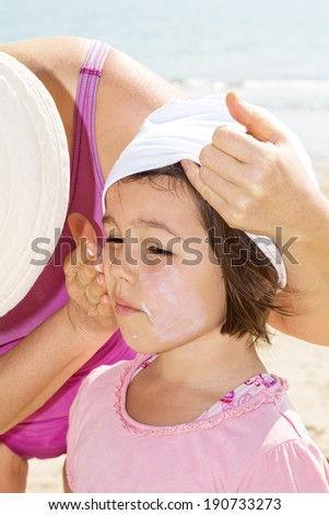 Mother applying sunblock  on her daughter - stock photo