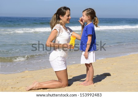 Mother applying sunscreen on child on the beach - stock photo
