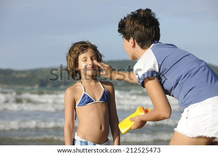 Mother applying sunscreen to daughter at beach - stock photo