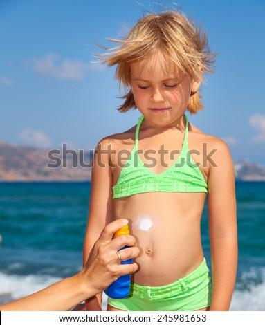 Mother applys sunblock cream to her  daughter - stock photo